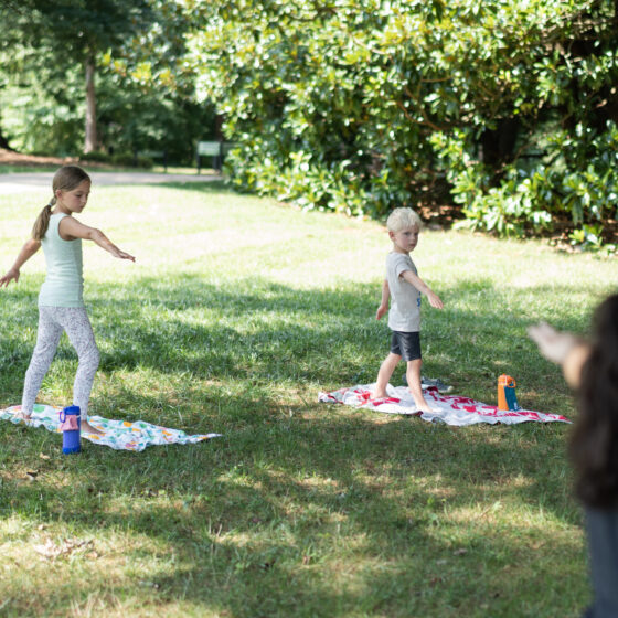 Two children stand on colorful mats outside and do a yoga pose.