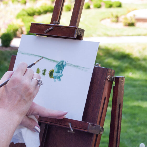 A person's hand poised over a canvas mounted on an easel.