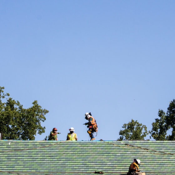 A group of people in construction gear on top of a green tile roof.