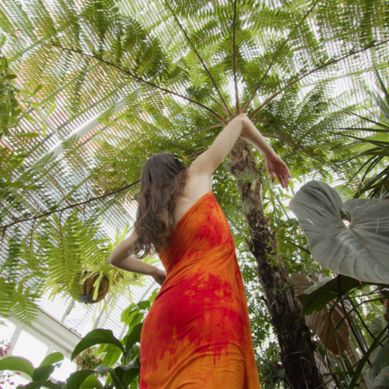 A woman in a red and orange dress stretching her arms above her head under a huge palm tree.