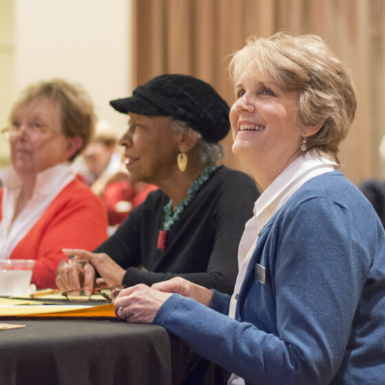 A woman sits smiling at a table with other docent-volunteers.