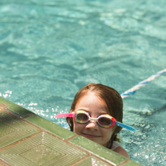 A child with goggles on swimming in a pool