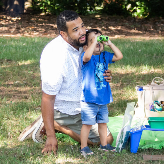 A young boy looks through binoculars as his father kneels beside him outdoors.