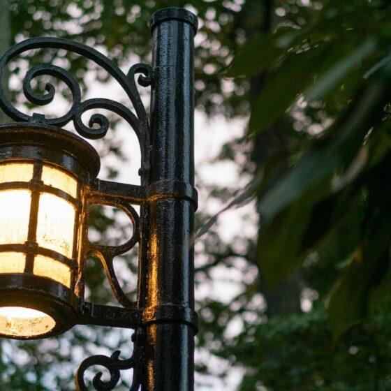 An antique street lamp lit up as dusk.