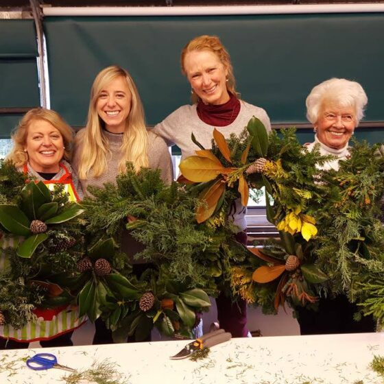 A group of four women hold up wreaths in front of a table.